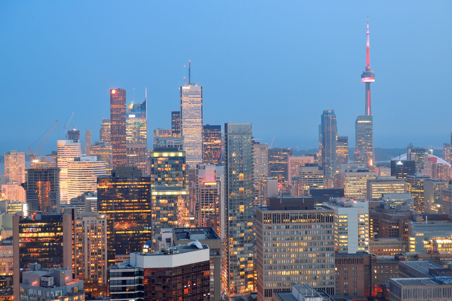 Toronto at dusk with city light and urban skyline with skyscrapers